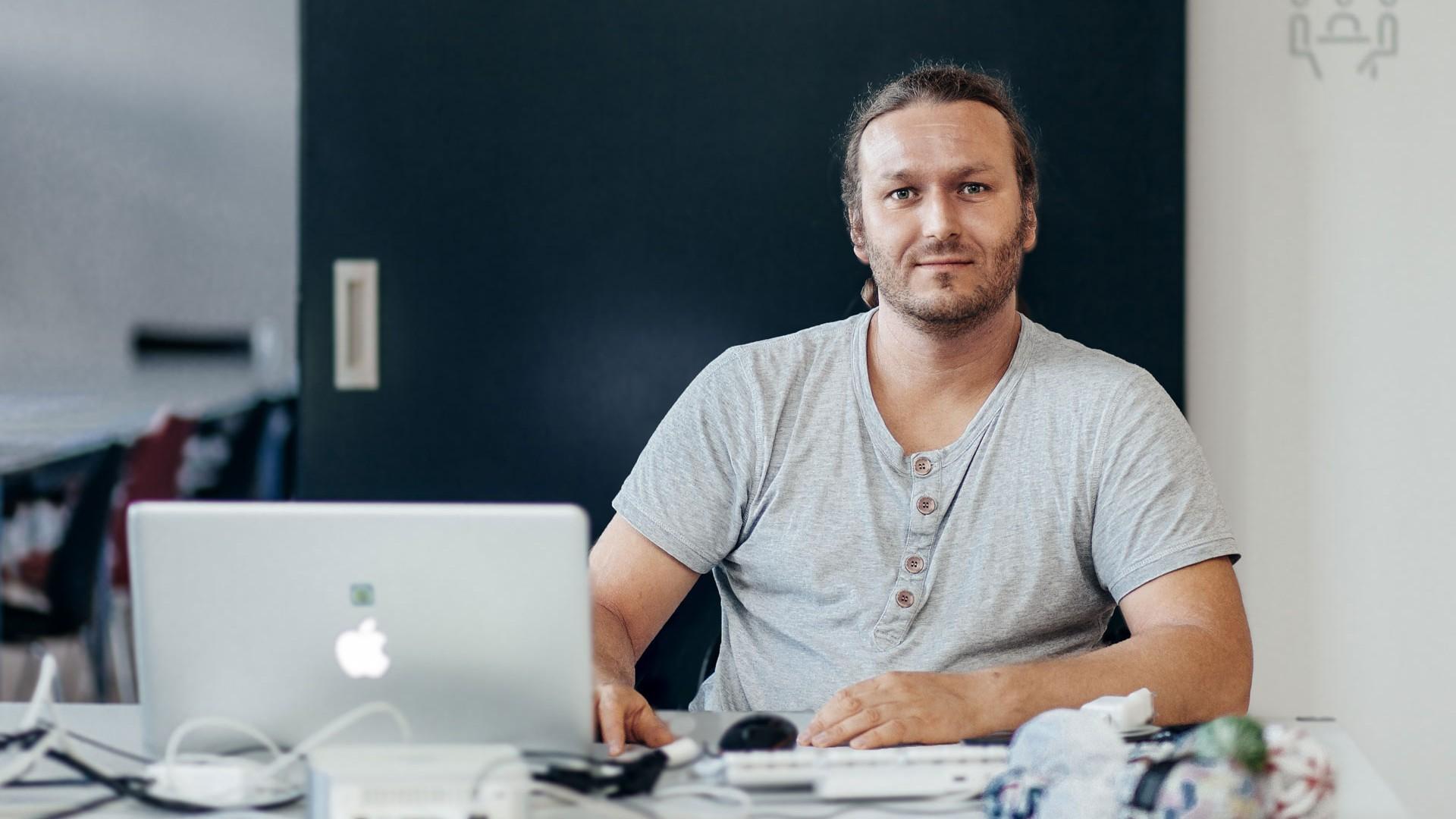 Björn sitzt im T-Shirt hinter seinem Laptop und allerlei weiteren Geräten.