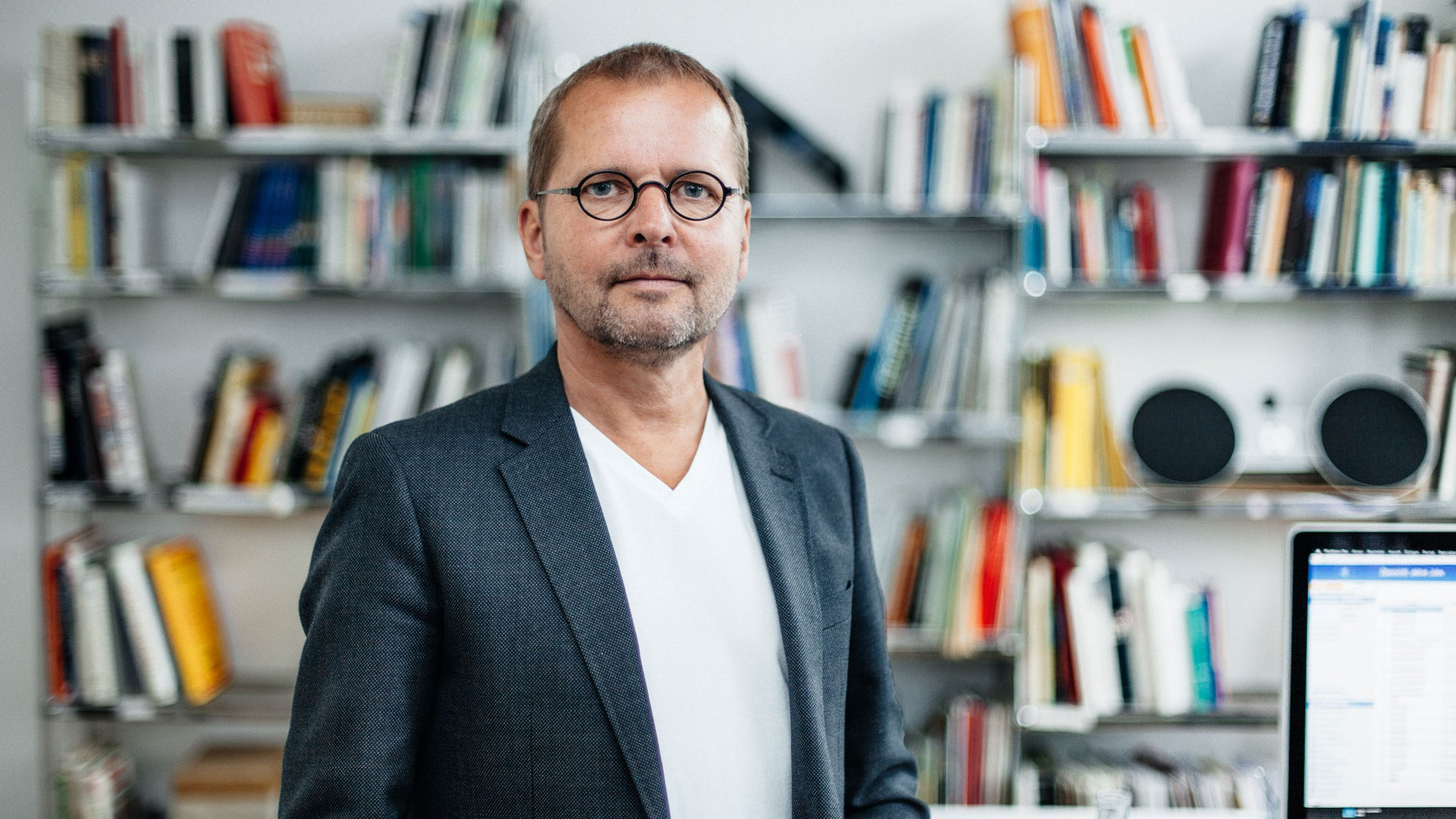 Florian is standing in front of the bookshelf in his office in a white T-shirt and dark jacket. He has a three-day beard and wears glasses with round lenses.
