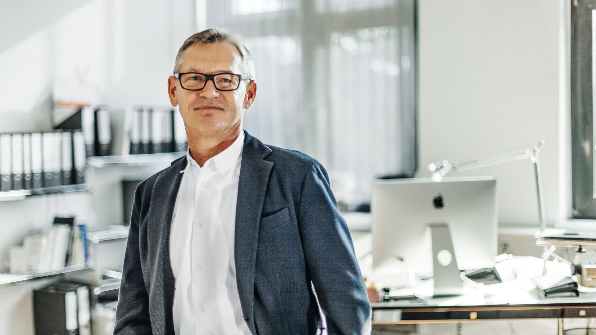 Hans-Peter steht in weißem Hemd und blauem Sakko vor seinem Schreibtisch.