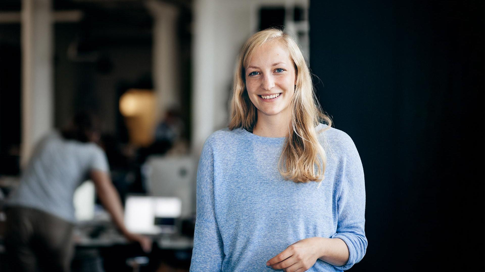 Johanna steht im Konferenzraum. Im Hintergrund arbeitet Björn an seinem Schreibtisch im Büro.