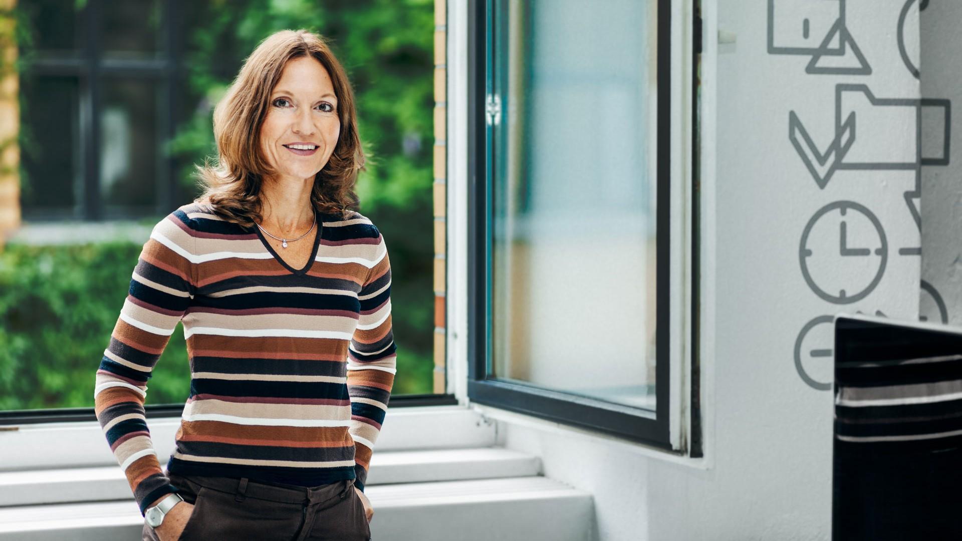 Katrin steht vor einem geöffneten Fenster mit Blick ins Grüne.