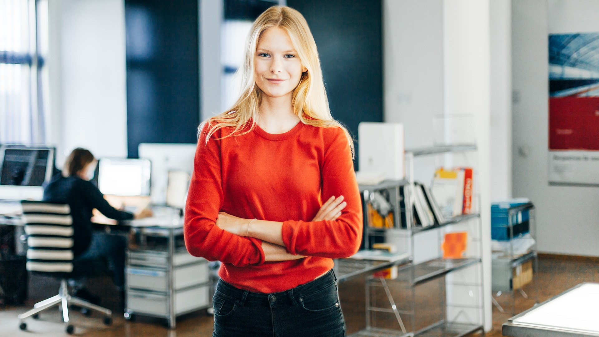 Das ist Pia. Sie hat lange blonde Haare und trägt einen roten Pulli. Im Hintergrund sieht man unscharf ein Bücherregal und Schreibtische mit Monitoren.