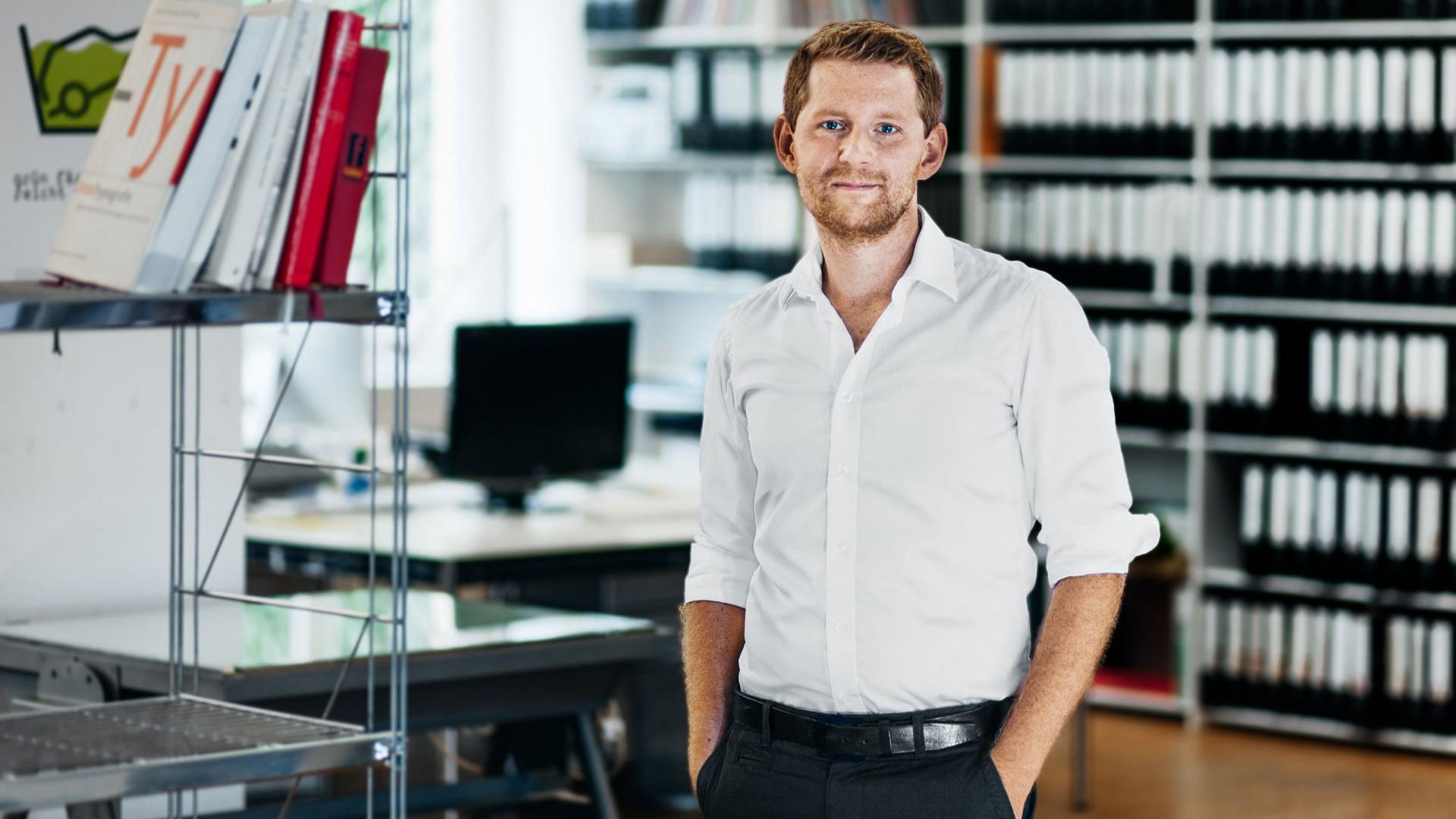 Tim steht in weißem Hemd zwischen Arbeitstischen und Bücherregalen im Büro.