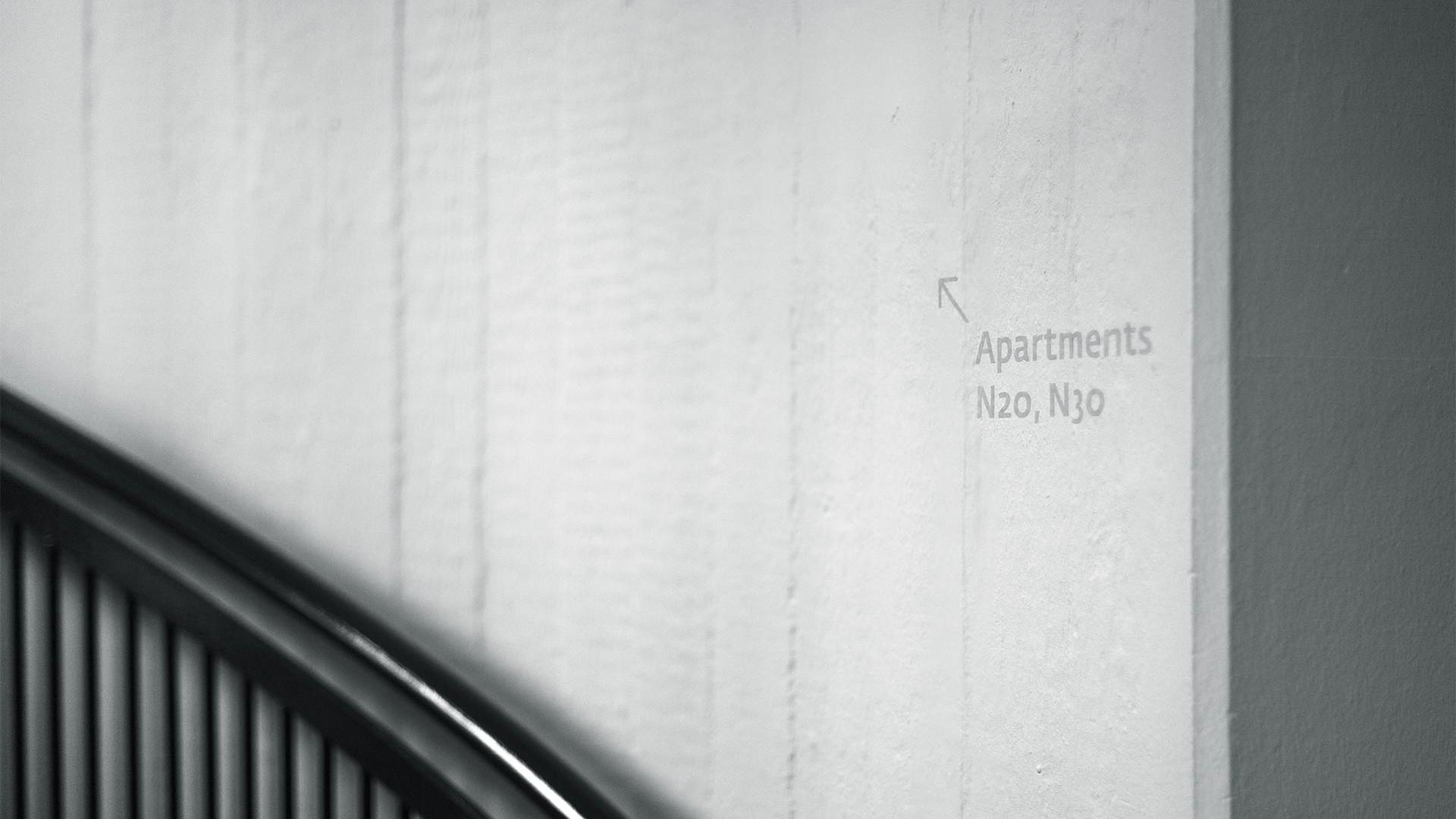 Auf einer rohen Betonwand mit einem schwarzen Treppengeländer verweisen dezente, hellgraue Buchstaben auf die Apartments im ersten Stock.